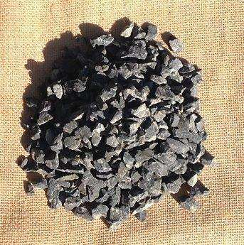 A pile of 10mm black basalt stones, on top of a hessian bag