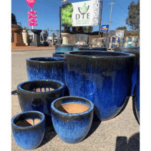 A bunch of bright blue pots with a gradient tone, in a variety of sizes, from small to large
