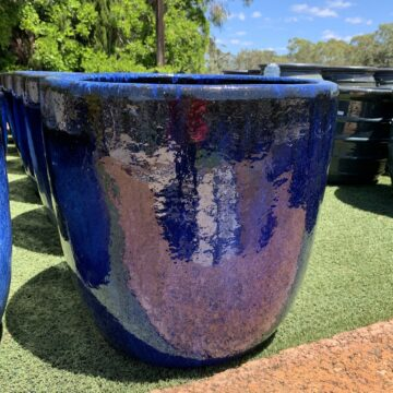 A bunch of bright blue pots all in one line, the colour goes from bright blue to light blue